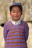 vertical stock photography | China, Gansu Province, Young boy and lambskins, Linxia, image id 4-117-1