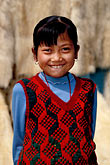 vertical stock photography | China, Gansu Province, Young girl and lambskins, Linxia, image id 4-117-3