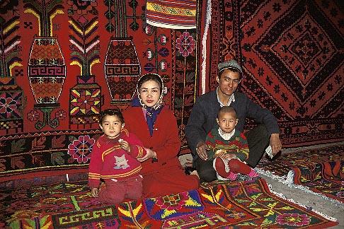 image 4-161-8 China, Turpan, Uighur family selling carpets in bazaar