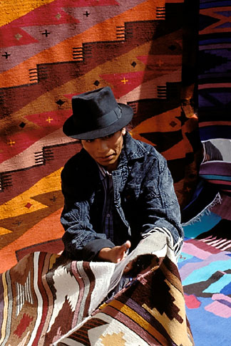 image 2-4-2 Ecuador, Otavalo, Weaver selling his rugs in the market