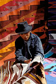 fabric stock photography | Ecuador, Otavalo, Weaver selling his rugs in the market, image id 2-4-2