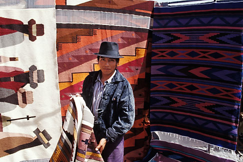 image 2-4-3 Ecuador, Otavalo, Weaver selling his rugs in the market