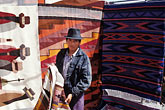 fabric stock photography | Ecuador, Otavalo, Weaver selling his rugs in the market, image id 2-4-3