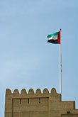 vertical stock photography | United Arab Emirates, Fujairah, Fujairah Fort, crenellated watchtower with UAE flag, image id 8-730-400
