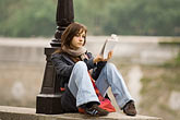 woman seated outside stock photography | France, Paris, Reading on the bank of the Seine, image id 6-450-5840