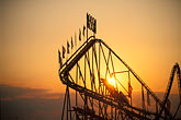 rollercoaster stock photography | Germany, Munich, Oktoberfest, Rollercoaster at sunset, image id 3-953-14