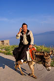 sunlight stock photography | Greece, Hydra, Man on donkey with cell-phone, image id 3-701-39