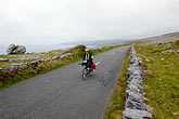 one person stock photography | Ireland, County Clare, Bicycling near Black Head in the Burren, image id 4-900-960