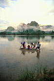 vertical stock photography | Laos, Vang Vieng, Women washing clothes in the river, image id 8-581-25