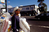 person stock photography | California, Oakland, Fruitvale, Pillow vendor, International Blvd., image id 9-444-78