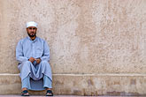 serene stock photography | Oman, Buraimi, Arab man, seated against wall, image id 8-730-1836