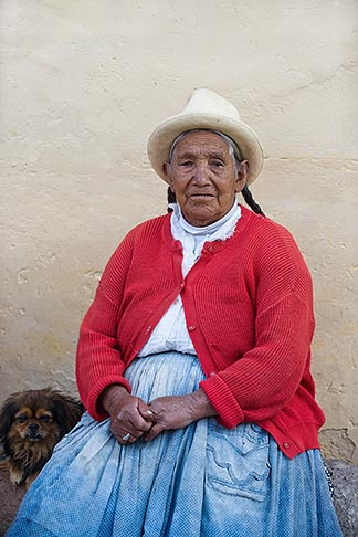 image 8-760-1274 Peru, Ollantaytambo, Senior Quechua woman, seated outdoors, with hat and red pullover, front view