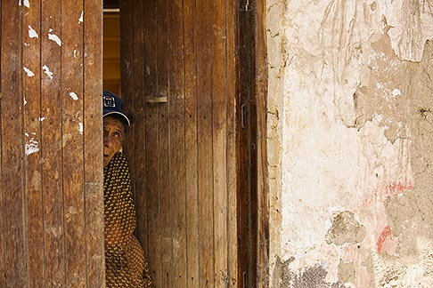 image 8-760-1353 Peru, Ollantaytambo, Woman with peeking from behind half open wooden door