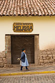 shop stock photography | Peru, Cuzco, Quechua woman walking outside shop, image id 8-760-769