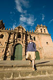 vertical stock photography | Peru, Cuzco, Tourist descending steps in front of Cuzco Cathedral, low angle view, image id 8-761-988