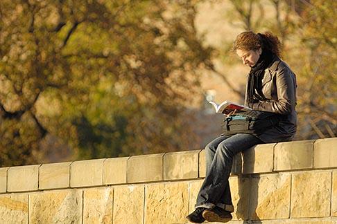 image 7-730-8202 Poland, Krakow, Woman reading, sitting on embankment, Wael