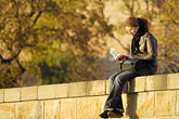 polish stock photography | Poland, Krakow, Woman reading, sitting on embankment, Wael, image id 7-730-8202