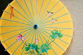 centred stock photography | China, Shanghai, Yellow parasol with floral design, image id 7-620-4395