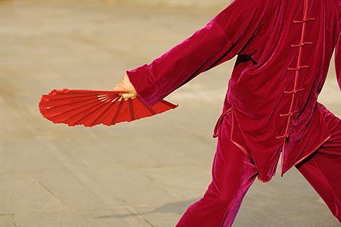 image 7-620-8986 China, Shanghai, Woman in red practising Tai Chi Fan