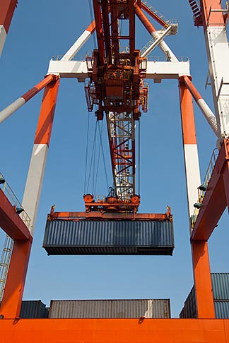 image 7-675-3906 Japan, Yokohama, Container crane lifting shipping container, low angle view