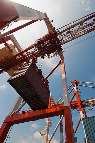 image 7-675-7979 Japan, Yokohama, Container crane lifting shipping container, low angle view