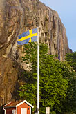 vertical stock photography | Sweden, Fjallbacka, Swedish flag and cliff, image id 5-710-5515