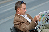 one man only stock photography | Sweden, Stockholm, Man reading on bench, image id 5-720-6124