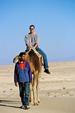 on foot stock photography | Tunisia, Nefta, Riding a camel, image id 3-1100-12