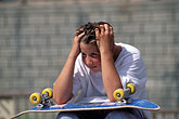 glum stock photography | Recreation, Young boy watching, tired, with skateboard, image id 6-235-18