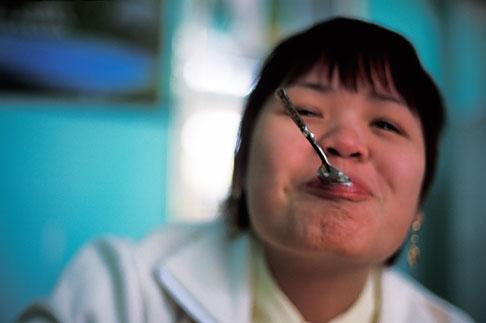 image S3-195-3 Vietnam, Moc Chau, Lady eating yogurt